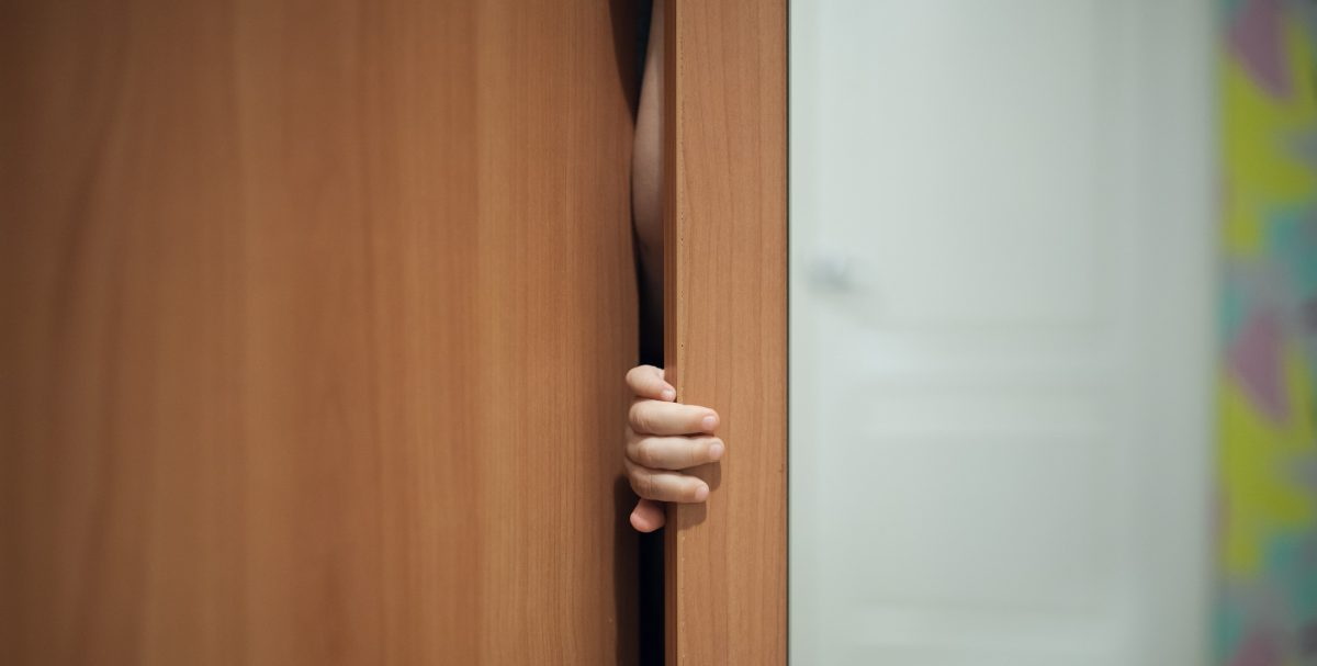 Photo of child playing peekaboo behind a door